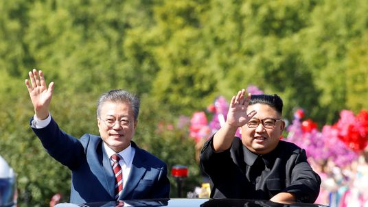 South Korean President Moon Jae-in and North Korean leader Kim Jong Un wave during a car parade in Pyongyang, North Korea