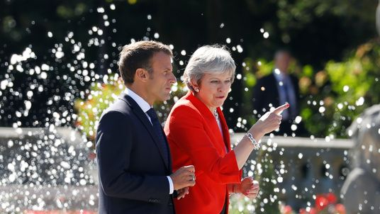 Theresa May and Emmanuel Macron arrive for a family photo during the European Union leaders informal summit in Salzburg