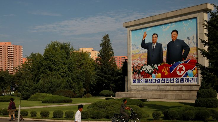 Residents pass by a painting featuring late North Korean leaders Kim Il-sung (L) and Kim Jong-il ahead of 70th anniversary of North Korea's foundation in Pyongyang