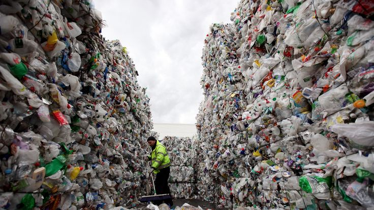 A recycling plant employee in London sweeps from inside a stack of plastic bottles