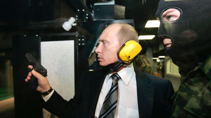 Mr Putin and a masked GRU agent at a shooting gallery in the GRU's headquarters in Moscow