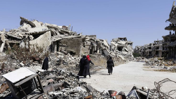 Three women walk among destroyed buildings in Homs