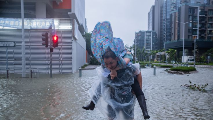 HONG KONG, HONG KONG - SEPTEMBER 16: A man carrying a woman cross a flooded road on September 16, 2018 in Hong Kong, Hong Kong. City officials raised the storm alert to T10, it's highest level,as Typhoon Mangkhut landed on Hong Kong. The strongest tropical storm of the season so far with winds as fast as 200 kilometres per hour, Mangkhut has reportedly killed at least 25 people in the Philippines as it continues it's path towards southern China. (Photo by Lam Yik Fei/Getty Images)