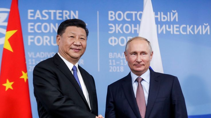Russian President Vladimir Putin shakes hands with Chinese President Xi Jinping