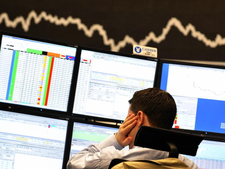 A broker looks at his screens