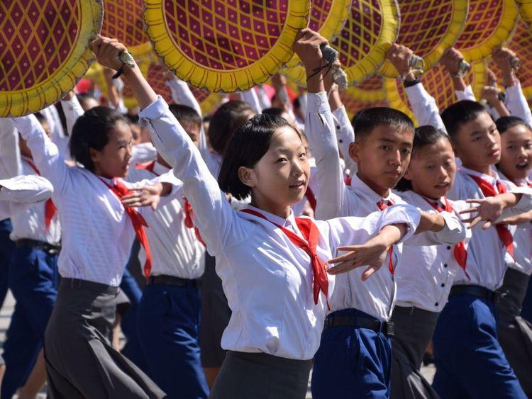 Schoolchildren dance during the parade in North Korea