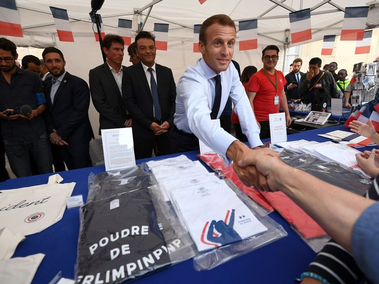 French President Emmanuel Macron shakes hands with visitors next to items for sale at the Elysee Palace