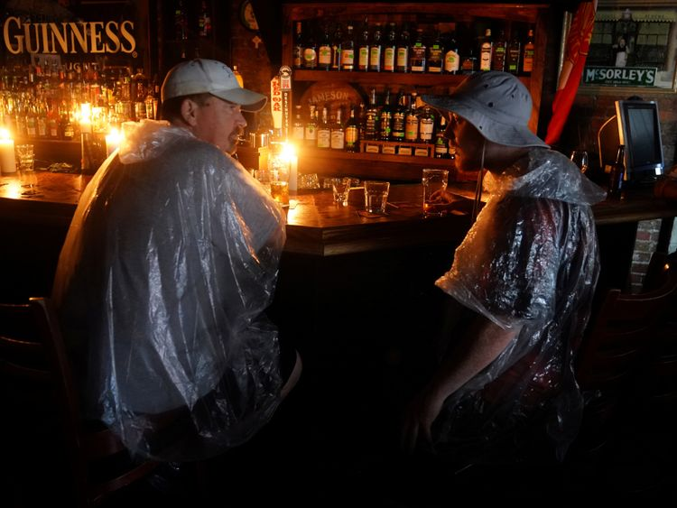 """People sit at a bar that has no power and drink during a """"Hurricane Party"""" as Hurricane Florence comes ashore on Wilmington, North Carolina, U.S., September 14, 2018"""
