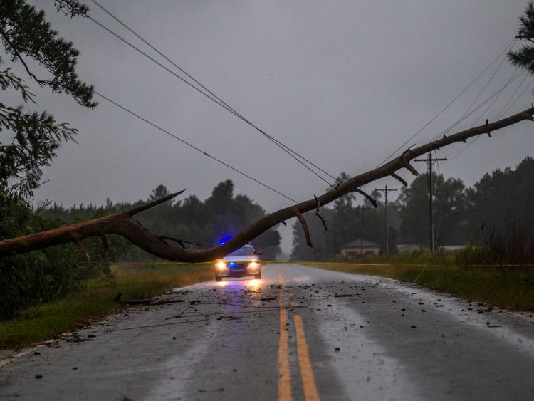 FLORENCE, SC - SEPTEMBER 14: A law enforcement officer blocks traffic from a downed tree on rural South Carolina state highway 51 on September 14, 2018 near Florence, South Carolina. The storm made landfall as a category 1 hurricane but has since been downgraded to a tropical storm. (Photo by Mark Wallheiser/Getty Images)