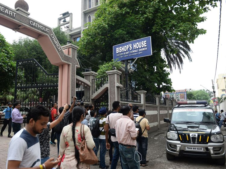 Indian media gather around police vehicle in front of bishop's house to cover the Kerala state police investigation
