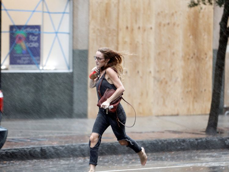 A woman runs past boarded up and taped store fronts during the initial rains before the full arrival of Hurricane Florence in Wilmington, North Carolina