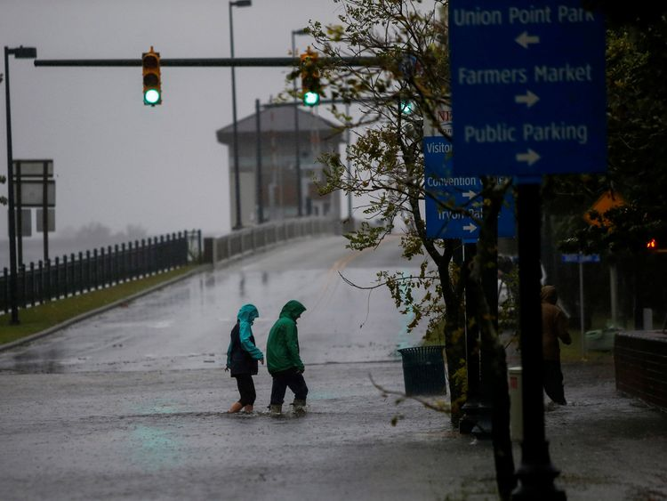 People walk on a local street as water from Neuse River starts flooding houses in New Bern, North Carolina