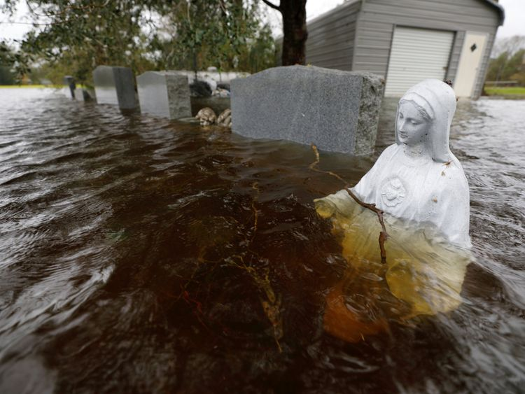 A Christian statuette is partially submerged in rising flood waters inundating a cemetery in the aftermath of Hurricane Florence, in Leland, North Carolina