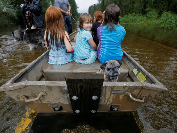 Iva Williamson, 4, peers behind her as she joins neighbours and pets in fleeing rising flood waters in the aftermath of Hurricane Florence in Leland, North Carolina