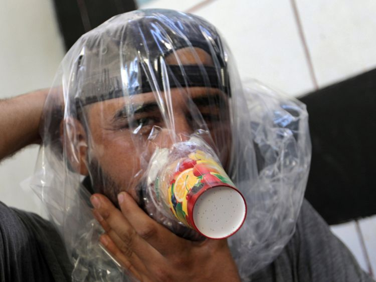 Hudhayfa al-Shahad tries an improvised gas mask in Idlib, Syria