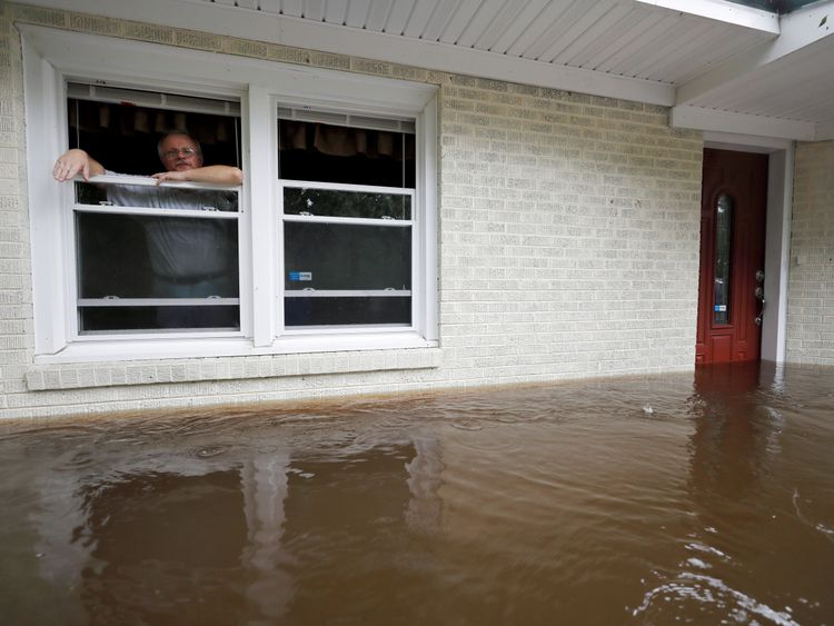 Obrad Gavrilovic peers out the window of his flooded home while considering whether to leave with his wife and pets as waters rise in Bolivia North Carolina U.S