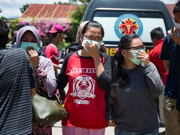 People wear masks as they attempt to identify the bodies of their relatives at the compounds of a police hospital