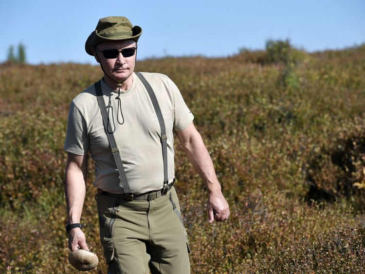 Vladimir Putin holds a mushroom he has picked while holidaying in Siberia