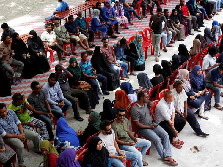 People sit in line as they wait to cast their votes at a polling station during the presidential election in Male, Maldives September 23, 2018