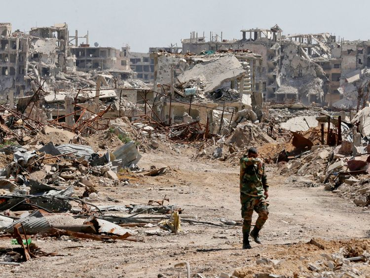 A Syrian regime member walks amid the destruction in Eastern Ghouta in April 2018