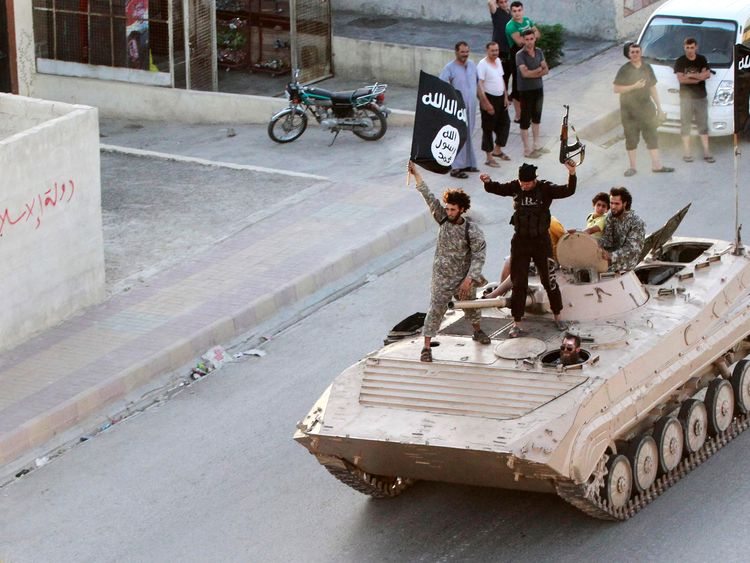 Islamic State fighters take part in a military parade in Raqqa province in June, 2014