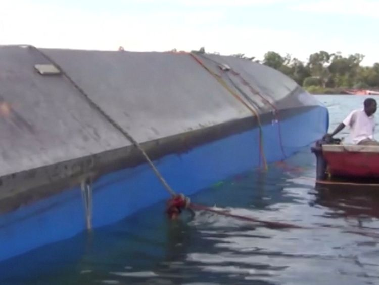 Rescue workers examine the hull of the ferry that overturned in Lake Victoria