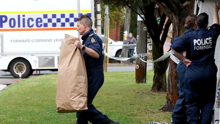 A police officer carries a bag from a property where five people were found dead in a suburb of Perth, Australia, September 10, 2018. AAP/Richard Wainwright/via REUTERS ATTENTION EDITORS - THIS IMAGE WAS PROVIDED BY A THIRD PARTY. NO RESALES. NO ARCHIVE. AUSTRALIA OUT. NEW ZEALAND OUT. NO COMMERCIAL OR EDITORIAL SALES IN NEW ZEALAND. NO COMMERCIAL OR EDITORIAL SALES IN AUSTRALIA.