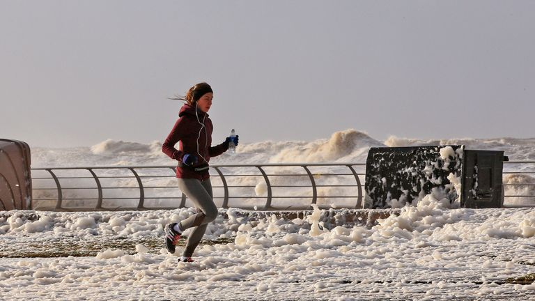 A woman jogs through sea foam in Blackpool as Storm Eleanor lashed the UK