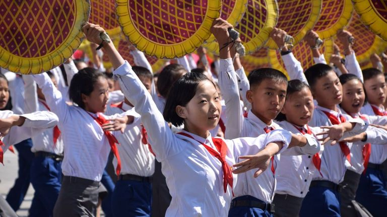 Schoolchildren dance during the parade in North Korea