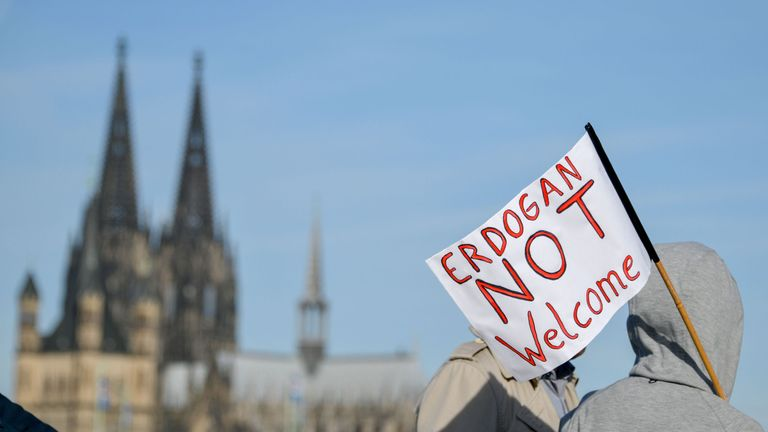 A woman walks with a banner reading 'Erdogan not Welcome' and Cologne's cathedral in the background prior to a demonstration on the theme Erdogan not welcome' prior to the visit of the Turkish President in Cologne, on September 29, 2018