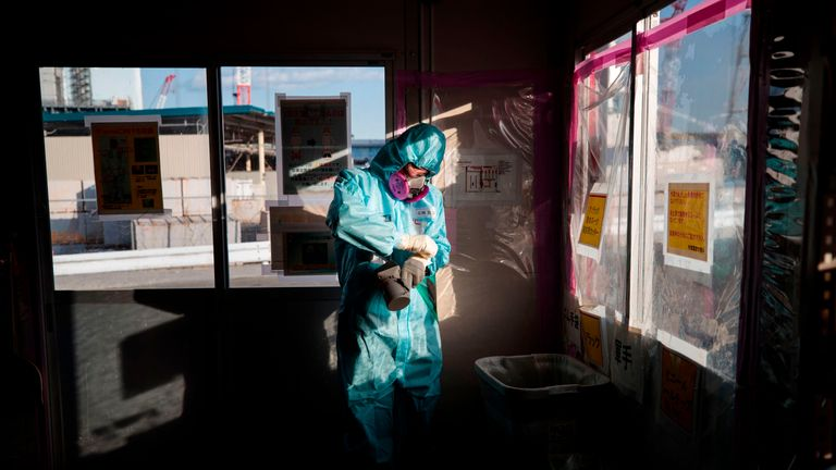 In this picture taken on January 31, 2018 an employee of Tokyo Electric Power Company (TEPCO) takes off his gloves as he holds a geiger counter to measure radiation after returning from a reactor building at Fukushima Dai-ichi nuclear power plant in Okuma, Fukushima prefecture
