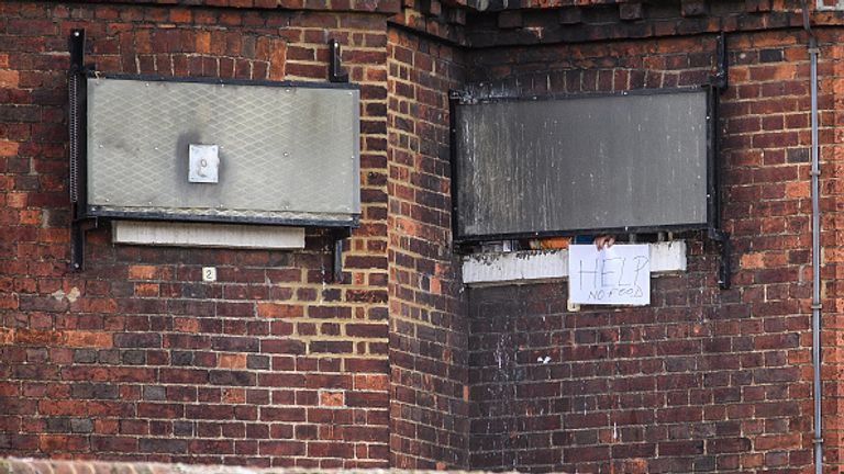 """BEDFORD, ENGLAND - NOVEMBER 07:  A man holds a sign, reading """"Help. No Food"""" from the window of HMP Bedford on November 7, 2016 in Bedford, England.  Reports suggest between 150 and 230 prisoners were involved in a riot, that lasted more than six hours, at the Category B men's prison HMP Bedford on Sunday, which left two prisoners injured.  (Photo by Leon Neal/Getty Images)"""