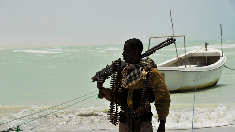 A Somali, part armed militia, part pirate, carries his high-caliber weapon on a beach in the central Somali town of Hobyo on August 20, 2010