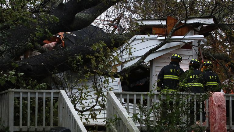 Firefighters arrive at a home where a large tree fell on that had three people trapped in Wilmington