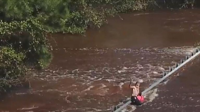 A couple, including a blind woman, got into difficulty crossing a flooded road until three men heard their calls and rescued them.
