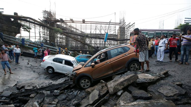 People stand next to the wreckage of vehicles at the site of a bridge that collapsed in Kolkata, India