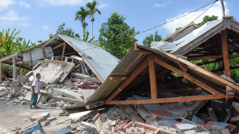 An Indonesian man examines the remains of houses, after a 6.4 magnitude earthquake struck, in Lombok