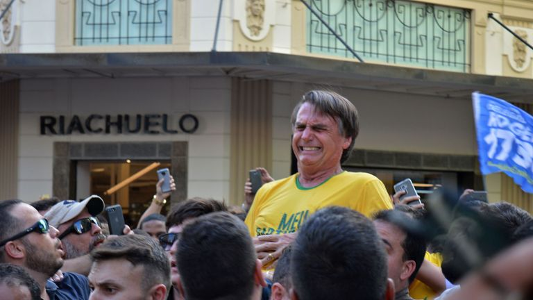 Brazilian right-wing presidential candidate Jair Bolsonaro gestures after being stabbed in the stomach
