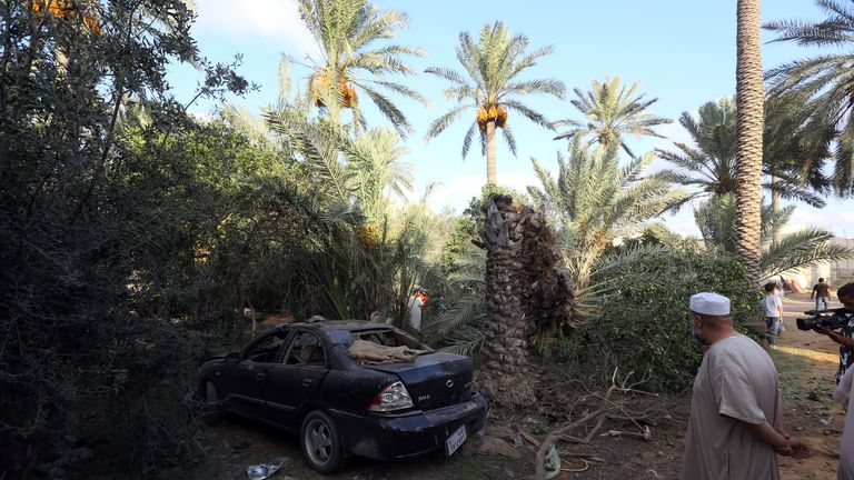 Libya stand near a site that was hit with a mortar shell amid violent clashes