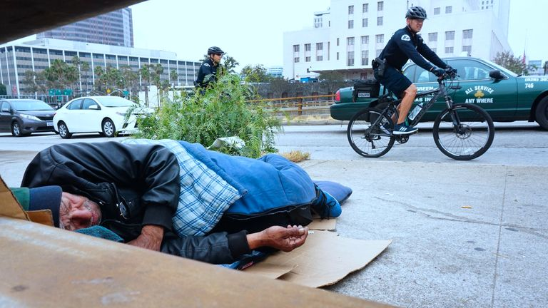 Los Angeles police officers cycle past a homeless man as he naps on the pavement