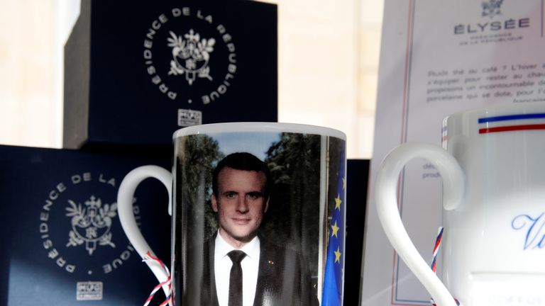 A mug with a picture of French President Macron and the Elysee Palace logo in the courtyard of the Elysee Palace