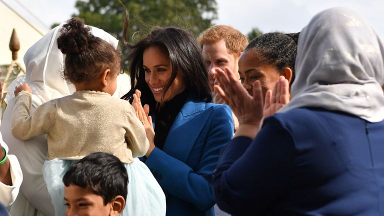 Meghan looked at home with the women as she played with one of their babies