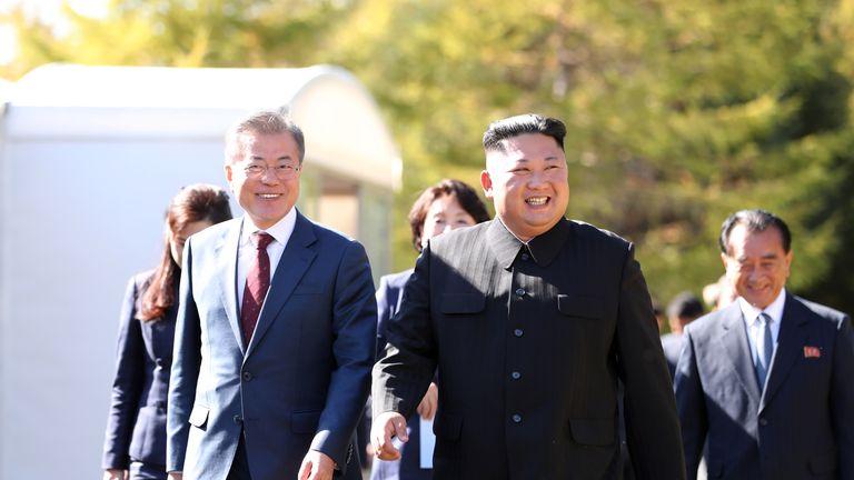 North Korea's leader Kim Jong Un (R) walk with South Korean President Moon Jae-in (L) during a visit to Samjiyon guesthouse in Samjiyon on September 20, 2018