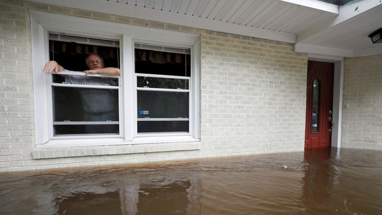 Obrad Gavrilovic peers out the window of his flooded home while considering whether to leave with his wife and pets, as waters rise in Bolivia, North Carolina, U.S
