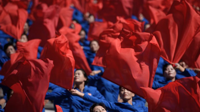 Participants wave flowers as they march past a balcony from where North Korea's leader Kim Jong Un was watching, during a mass rally on Kim Il Sung square in Pyongyang on September 9, 2018