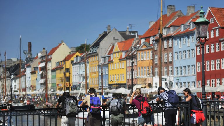 Tourists stand on a bridge and look at coulourful houses on August 10, 2010 in the district of Nyhavn in Copenhagen