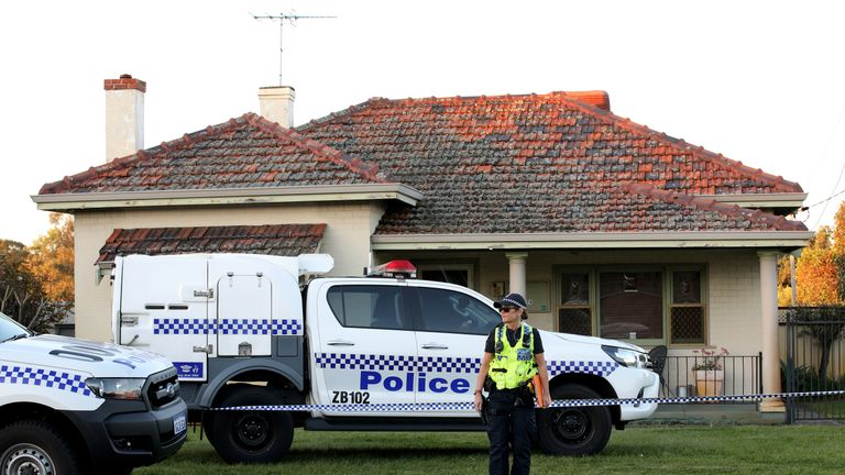 A police officer stands outside a property where five people were found dead in a suburb of Perth, Australia