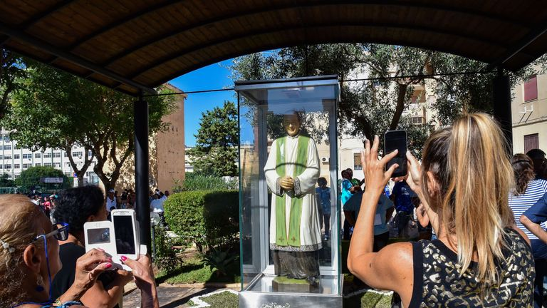 A statue of the murdered priest stands near the place where he was killed