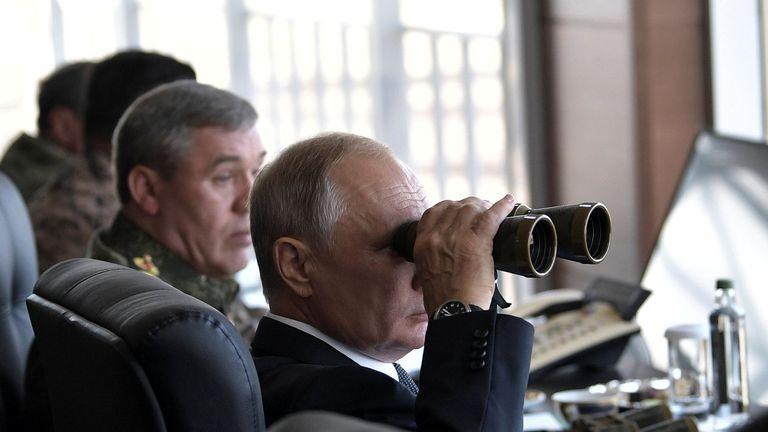 Russian President Vladimir Putin uses a pair of binoculars as he watches the Vostok-2018 (East-2018) war games