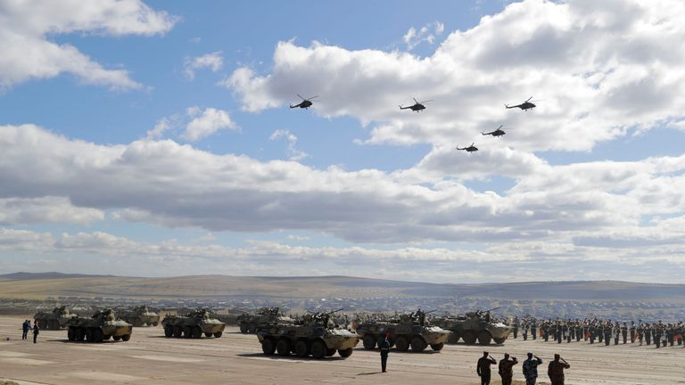 """Military vehicles and helicopters in motion during a parade on training ground """"Telemba"""""""